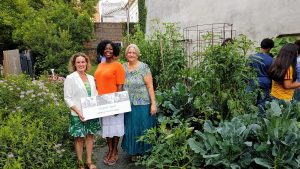 With our bountiful community garden as a summertime backdrop, Arm in Arm's Carolyn Biondi with UWGMC's Sandra Toussaint and Tarry Truitt.